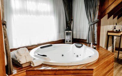 spa dans un abri en bois avec rideaux blancs aux fenêtres